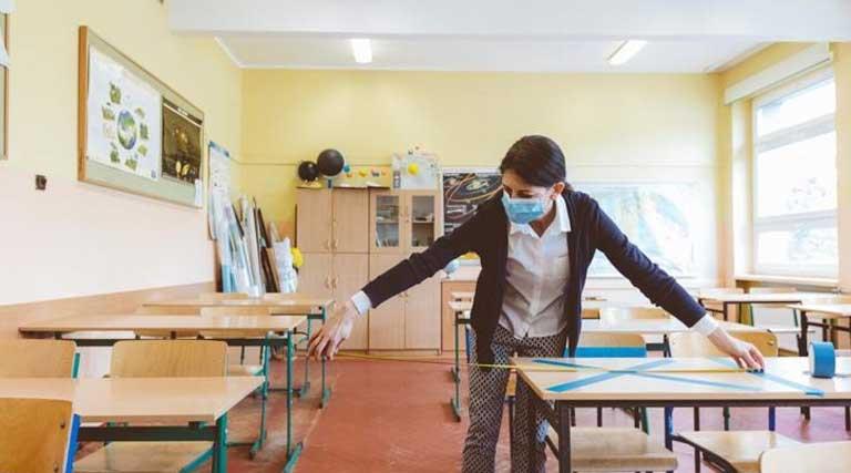 Teacher Wearing Mask Measures Distance Between Desks Social Distancing COVID-19
