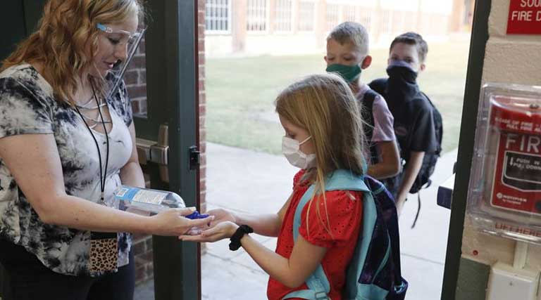 wearing masks prevent the spread of COVID-19 elementary school students use hand sanitizer before entering school for classes Godley, Texas.